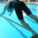 A swimmer diving into a pool at the start of a swim meet race.