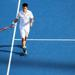 A tennis player standing on a tennis court beside his shadow.