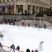 An outdoor skating rink in a city park filled with people