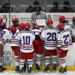 Wildcat hockey players huddle around coach, Chad Berman, as he draws up a play.