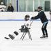Minnesota Special Hockey volunteer pushes a chair with a player who can't yet skate on their own.