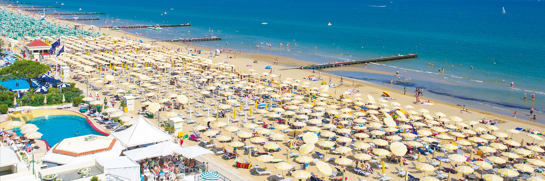 Lido di Jesolo, which is lined with parasols , and where many people take a swim in the turquoise Mediterranean Seasea.