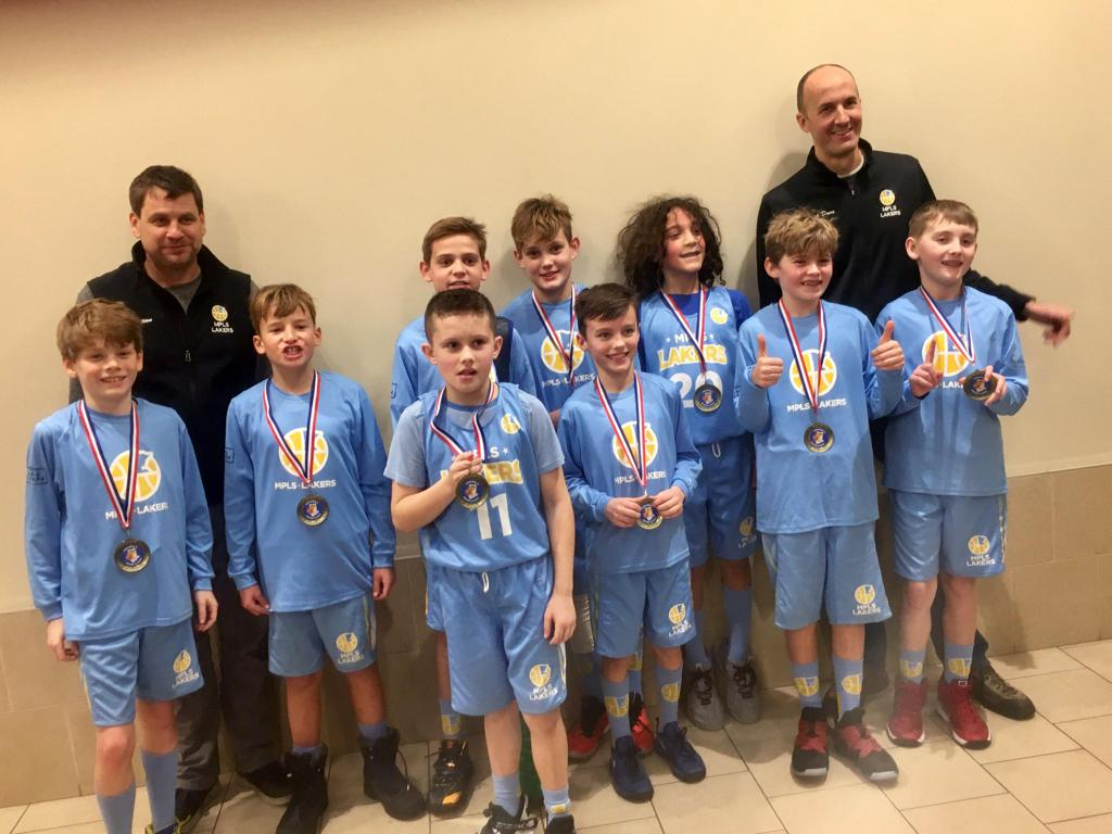 Minneapolis Lakers Boys 5th Grade White pose with their hardware after taking 1st at Concordia Winter Classic