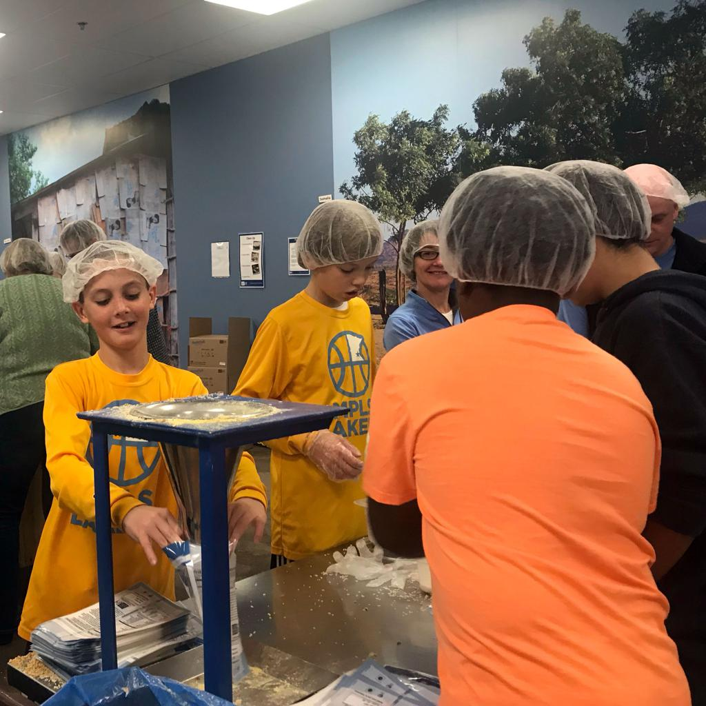 Mpls Lakers 6th grade boys players on the assembly line at Feed My Starving Children in Eagan, MN