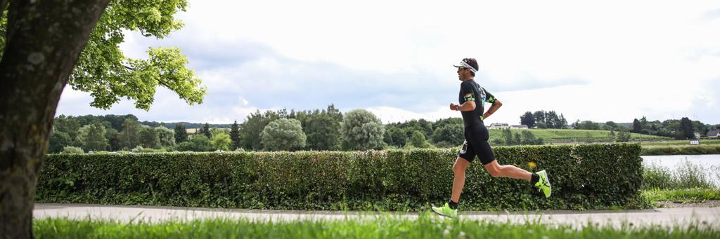 Athlete running along the flat course next to Moselle river and surrounded by scenic green nature in Luxembourg