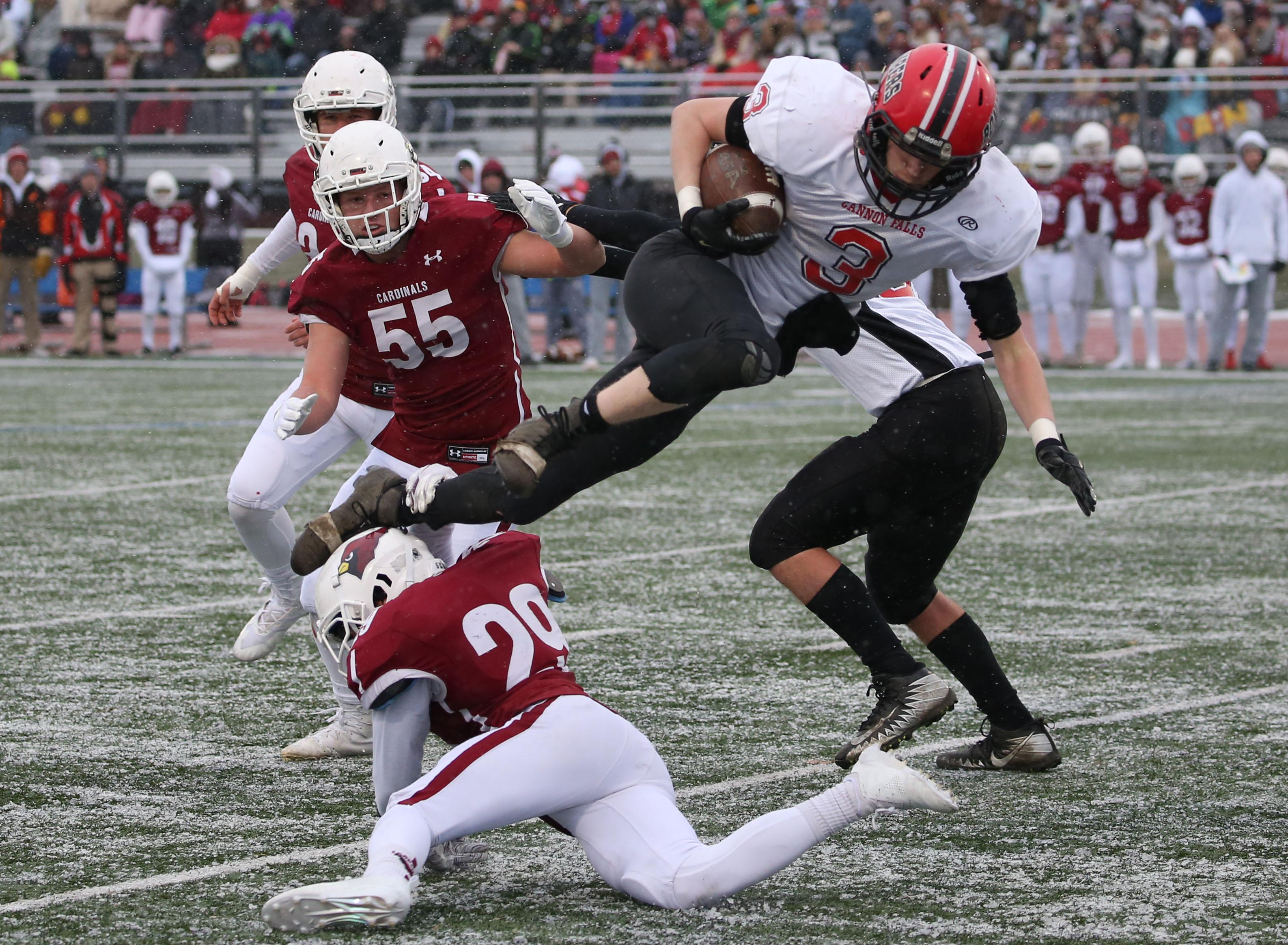 Brodie Hansen (3) leaps over Cardinal defenders for extra yardage. Hansen scored Cannon Falls' only touchdown of the first half to take a 7-6 lead into halftime. Photo by Cheryl Myers, SportsEngine