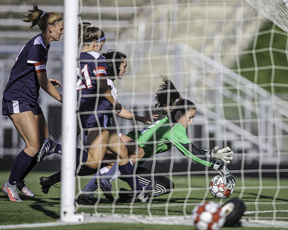 Orono goaltender Harper Randolph (in green) dived to stop a ball that had gotten past her just before it reached the goal line. Harper's save kept the game scoreless in the first half. Orono and Waconia finished in a 1-1 tie. Photo by Mark Hvidsten, Sport