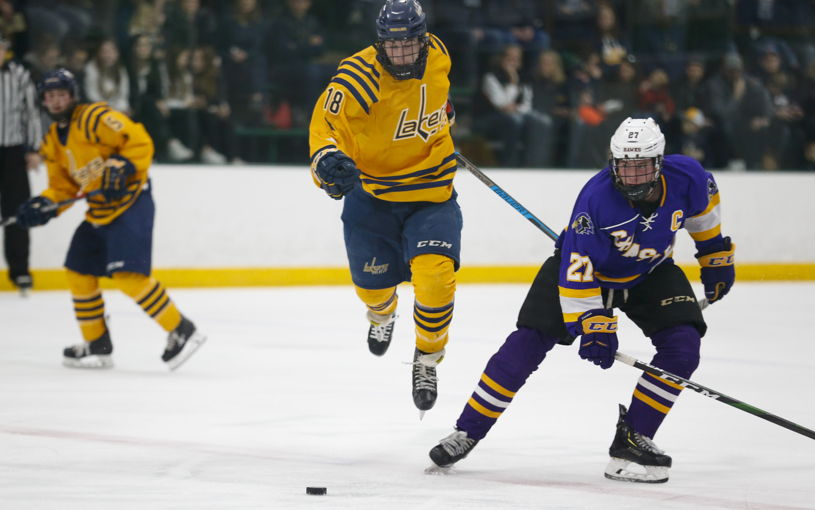 Prior Lake's Preston Lindholm (18) jumps around Chaska's William Magnuson (27) during the second period Saturday. The Lakers fell to the Hawks 4-1 in Edina. Photo by Jeff Lawler, SportsEngine