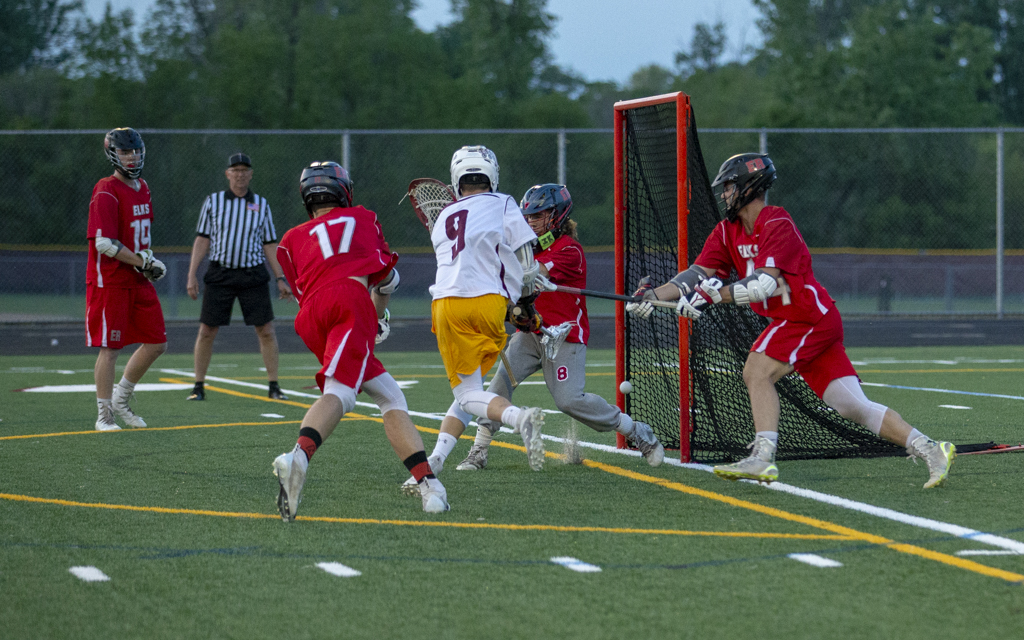 Irondale's Kevin Kvaal puts the shot past Elk River goalie Cody Simon for the game-winning goal in overtime. The Knights capped off an undefeated season with the 8-7 victory over the Elks. Photo by Jeff Lawler, SportsEngine
