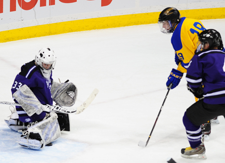 Thief River Falls' Tanner Nessen (19) looks for a rebound as New Ulm's Brach Kraus makes one of his 33 saves. Photo by Adam Crane