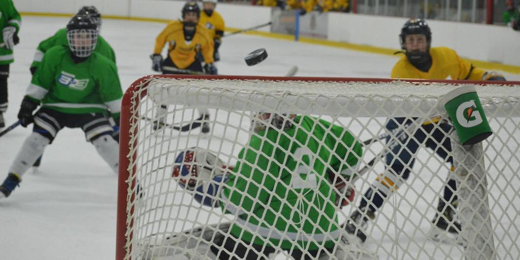 Youth hockey player taking a shot on net