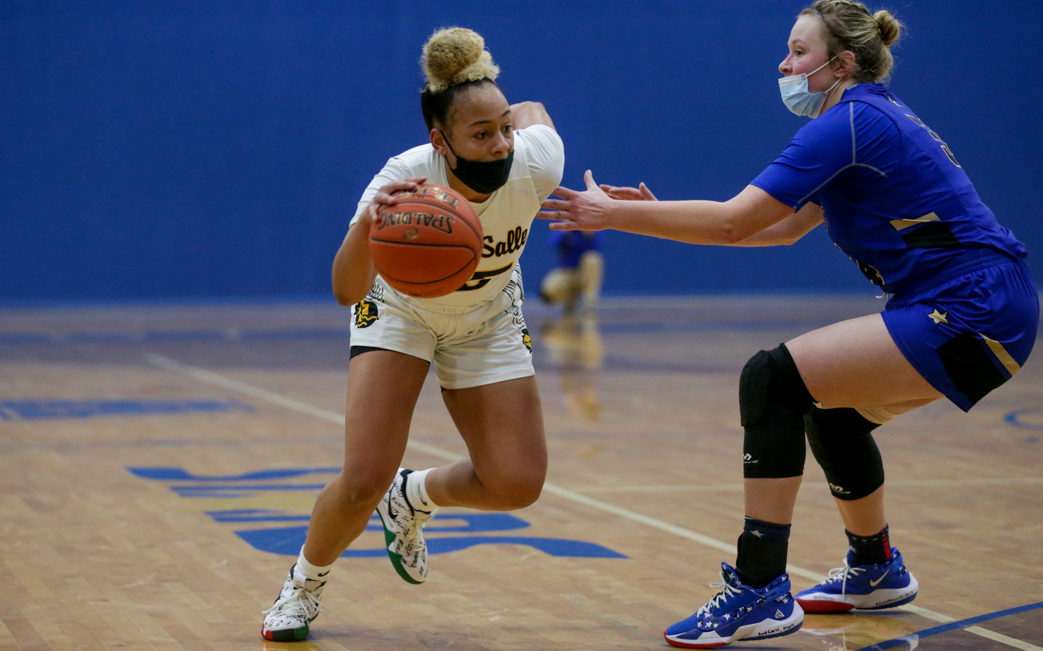 DeLaSalle's Sydney Runsewe (left) tries to dribble around Holy Angels' Rachel Kawiecki during Friday night's Tri-Metro Conference matchup in Richfield. The Islanders fell to the Stars 96-69. Photo by Jeff Lawler, SportsEngine
