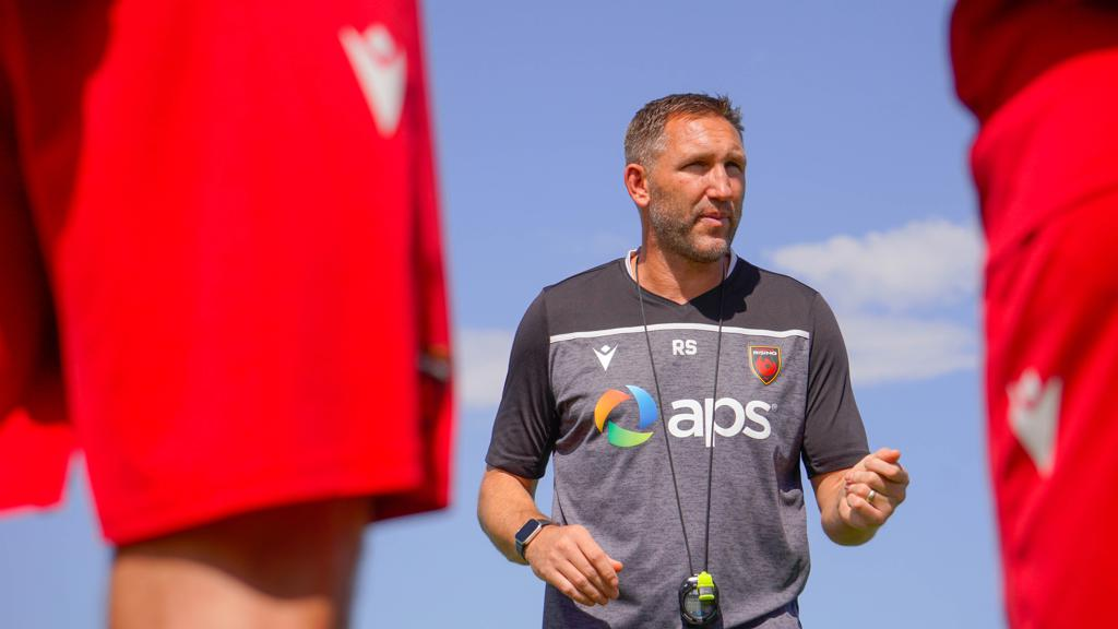 Shot of Rick Schantz from between two players as he speaks to players during training.