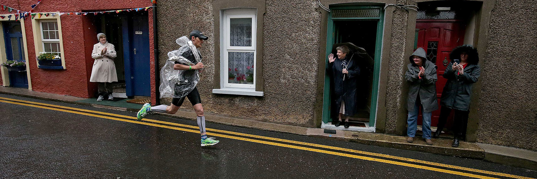 IRONMAN Ireland Cork athlete running through the city center of Youghal on a rainy day with people cheering him on
