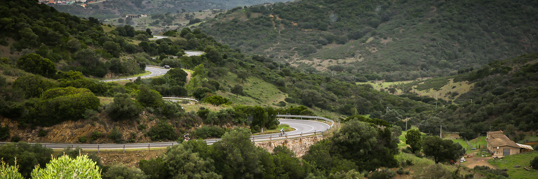IRONMAN 70.3 Sardegna athletes one their bike on winding streets surrounded by smalls hills and forests