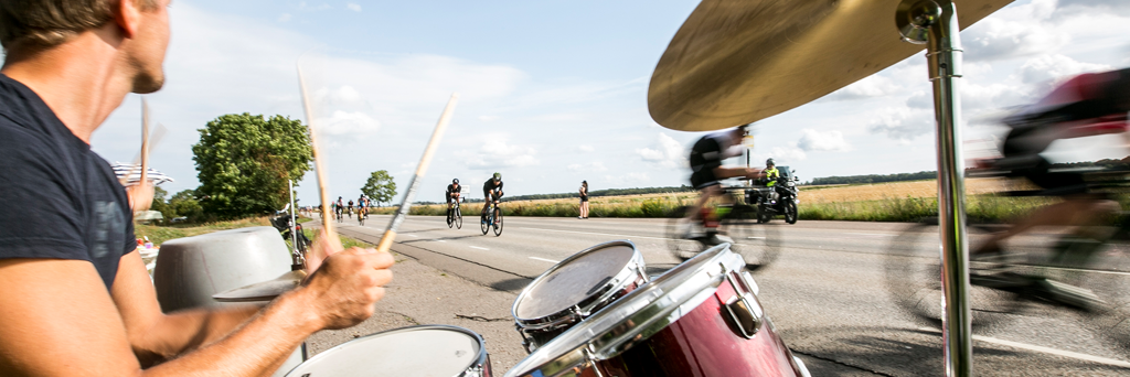 Men on their drums is making music and motivating athletes who bike past him in Kalmar Sweden