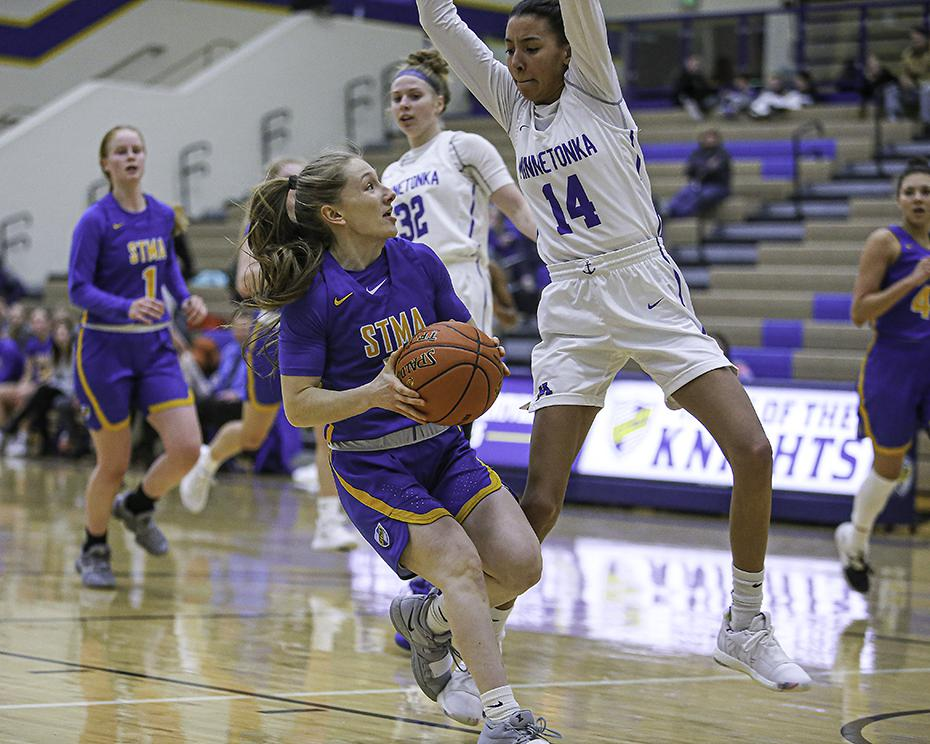 Sophomore Emma Miller had her path momentarily blocked by Minnetonka's Tori McKinney (14) as she drove to the basket. Miller scored 12 points. Photo by Mark Hvidsten, SportsEngine
