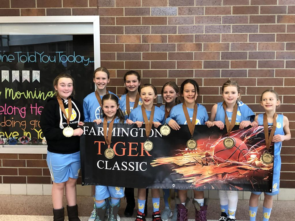 Mpls Lakers Youth Traveling Basketball Program Inc Girls 5th Grade Blue pose with trophies after earning 3rd place at the Farmington Girls Tiger Classic tournament in Farmington , MN