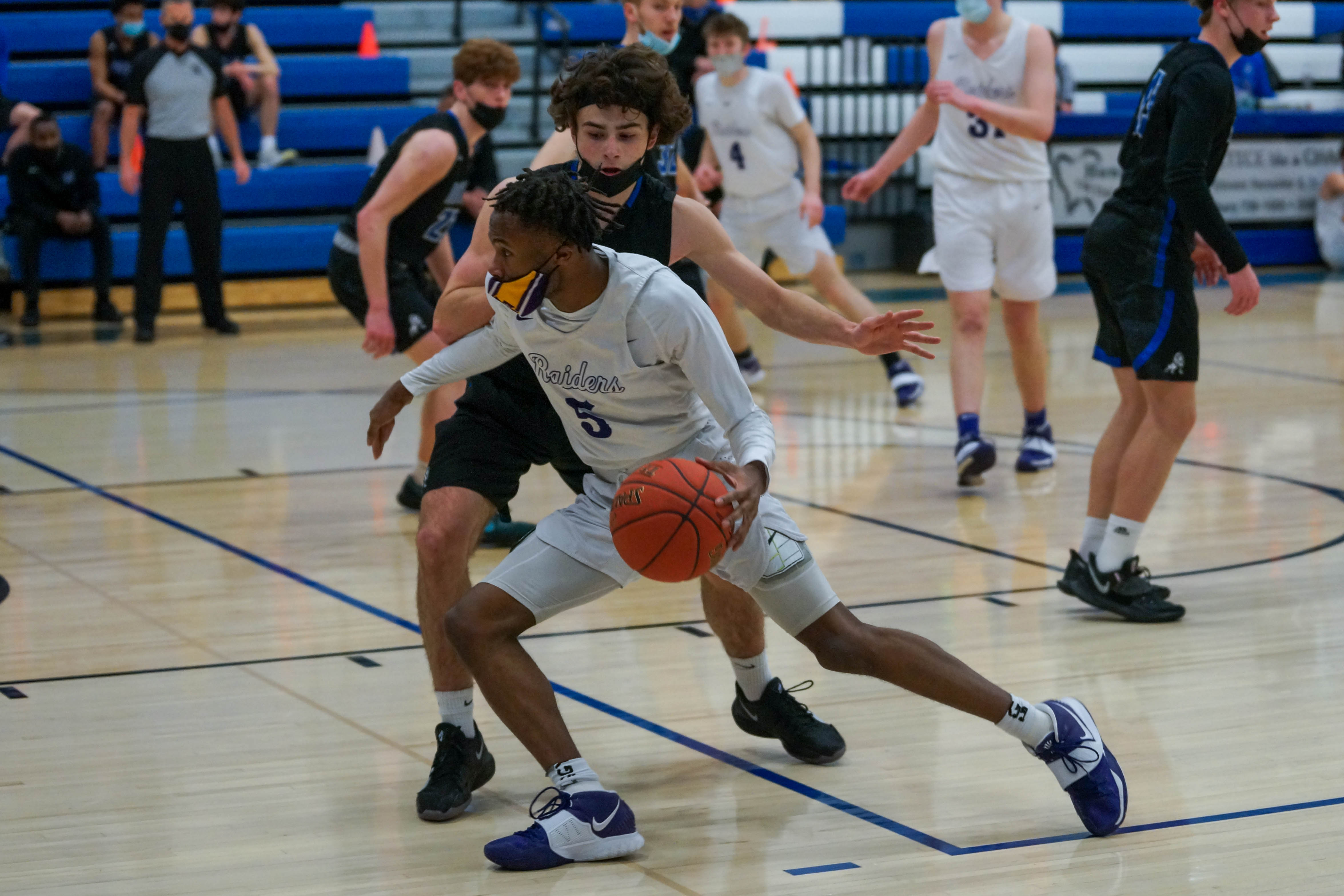 Cretin-Derham Hall's Tre Holloman (5) fends off Woodbury's Devin Padelford during play Friday night in the Class 4A, Section 4 championship game. Holloman scored 25 points in the Raiders' win over the Royals. Photo by Korey McDermott, SportsEngine
