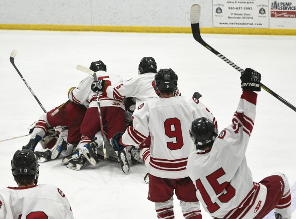 Concord players celebrate their team's double-overtime win over Bedford during the championship game of the Brian C. Stone Christmas Hockey Tournament at the JFK Coliseum in Manchester on Sunday. Thomas Roy/Union Leader