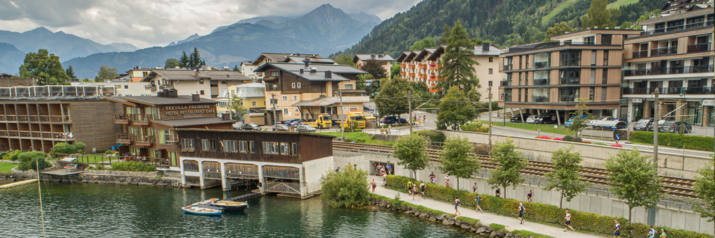 Athletes run along the shores of the spectacular Lake Zell at IRONMAN 70.3 Zell am See-Kaprun with hotels, houses and mountains in the background