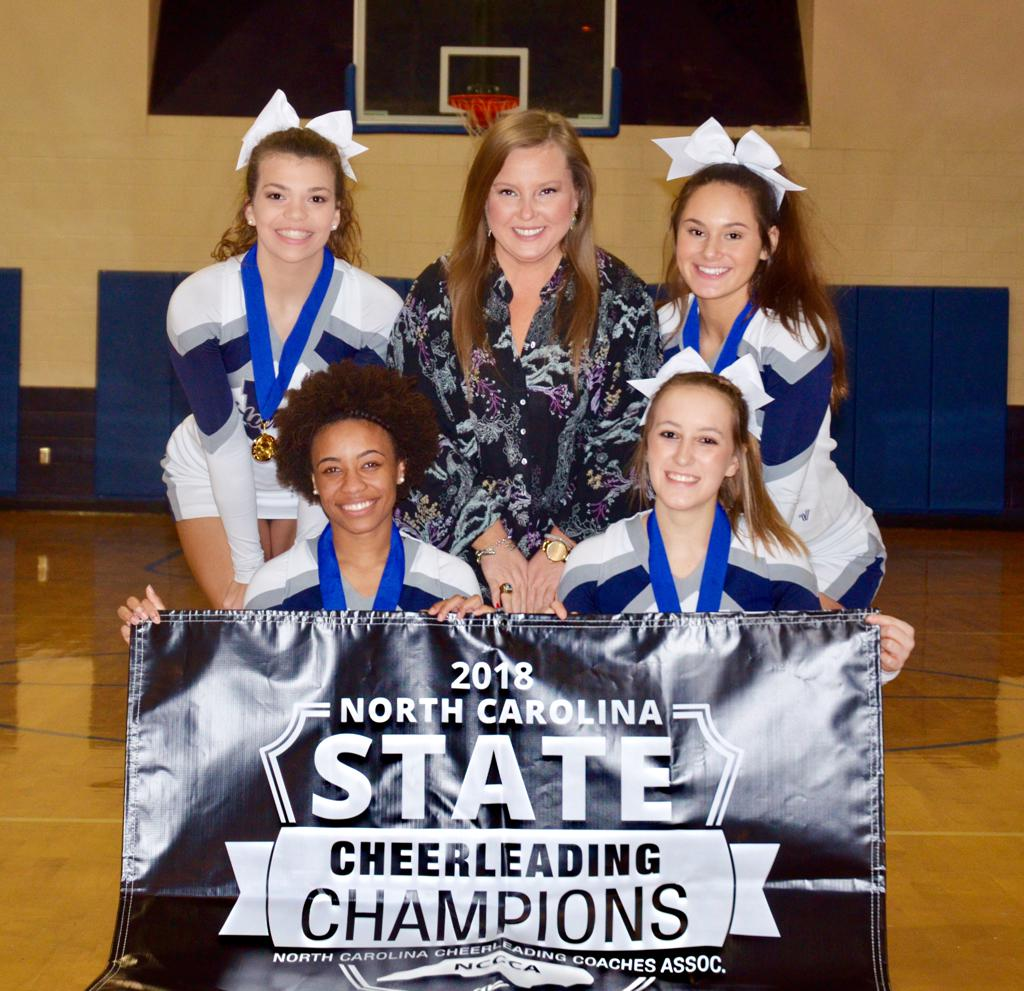 cheerleaders holding state championship banner