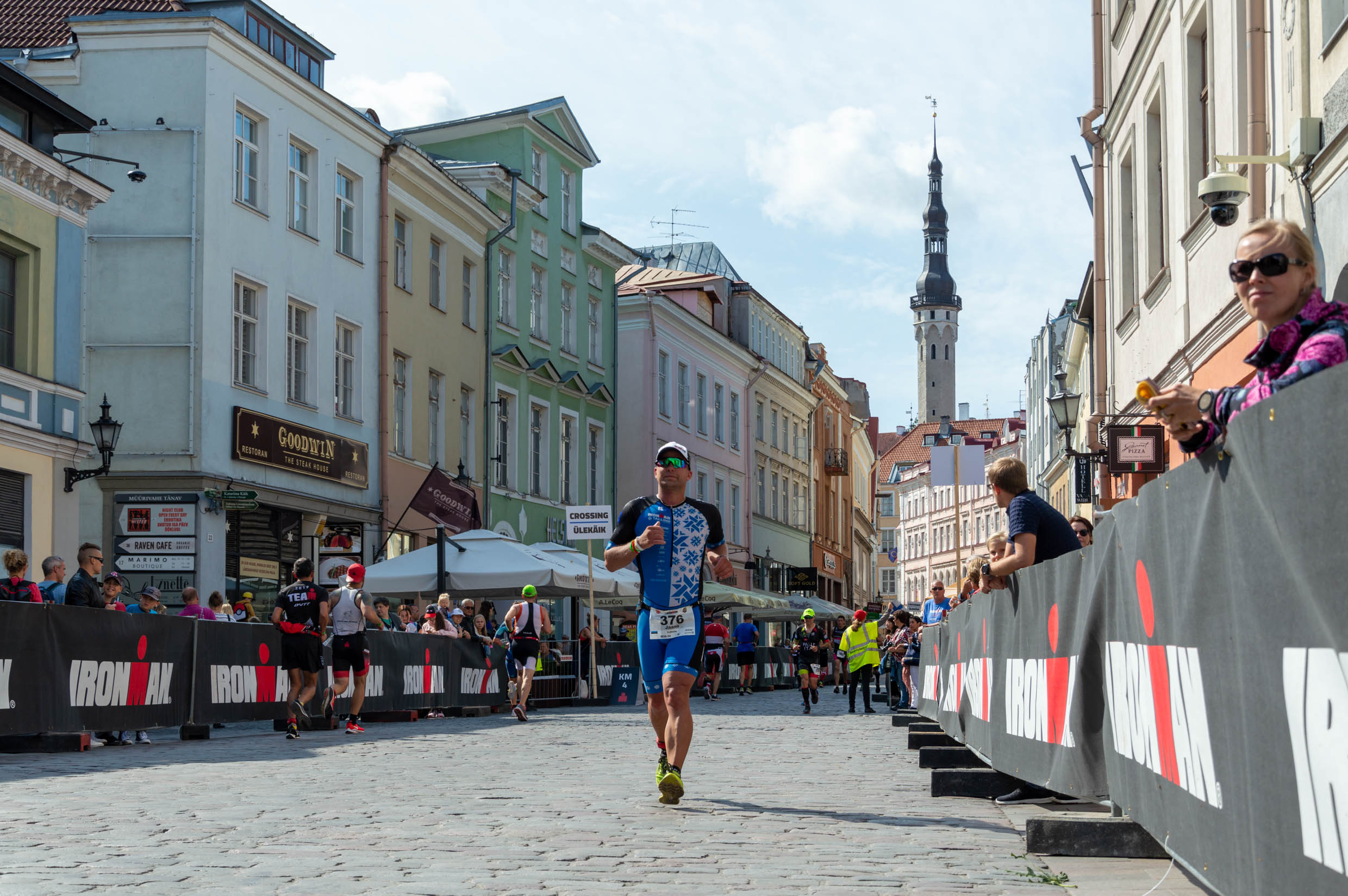 IRONMAN 70.3 Tallinn athletes running through the city of colorful houses and spectator standing on the side and cheering them on