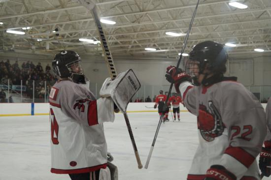 Stillwater's T.J. Sagissor and goaltender Josh Benson celebrate after Sagissor scored his fourth goal of the game in a 6-5 win over Lakeville North. Credit: Peter Odney.