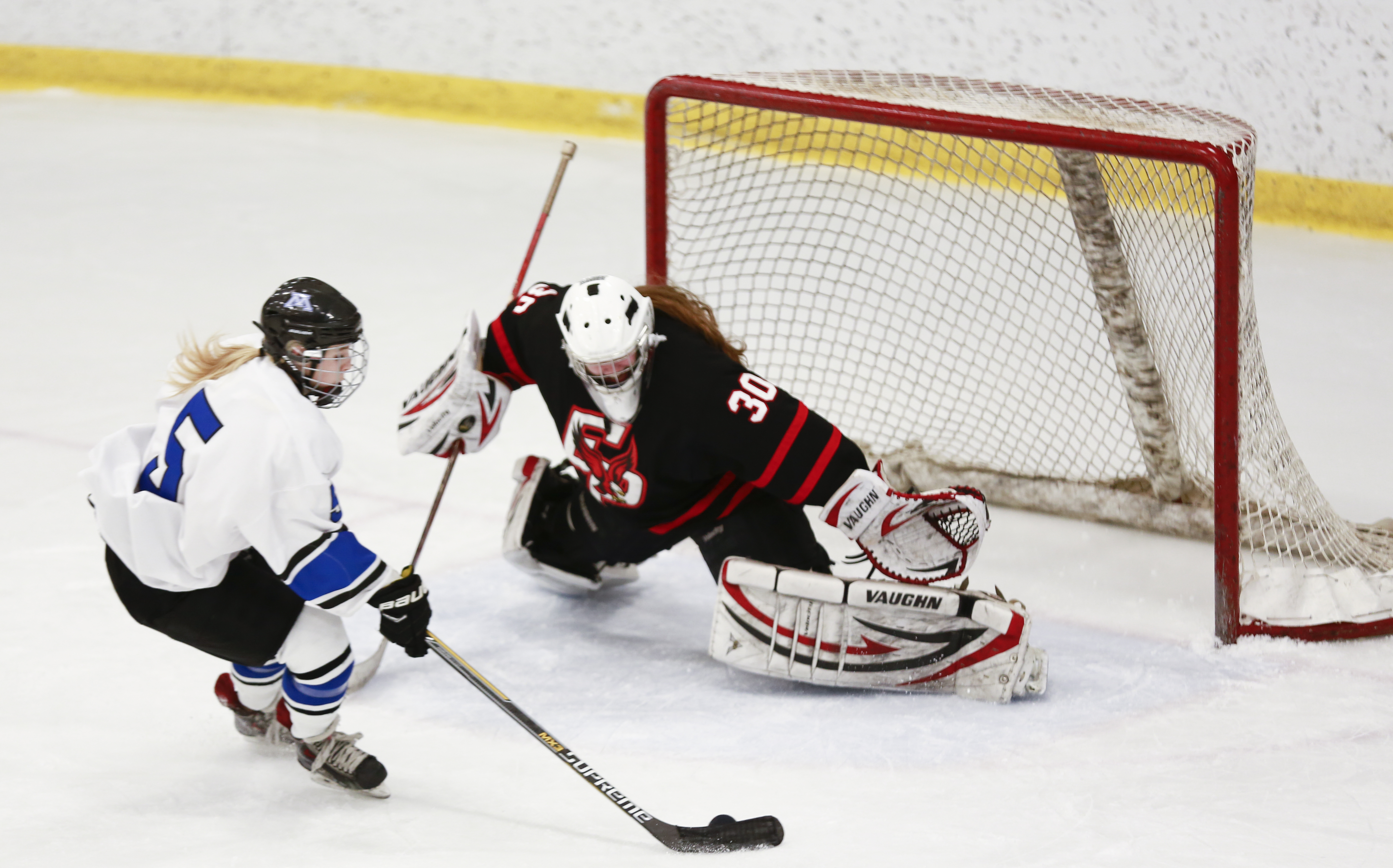 Minnetonka's Presley Norby (5) rushes to the Eagles goal to score against goaltender Alexa Dobchuk (30). Norby scored 3 goals during the game earning a hat trick and leading the Minnetonka Skippers to a victory at home, 3-2. Photo by Chris Juhn