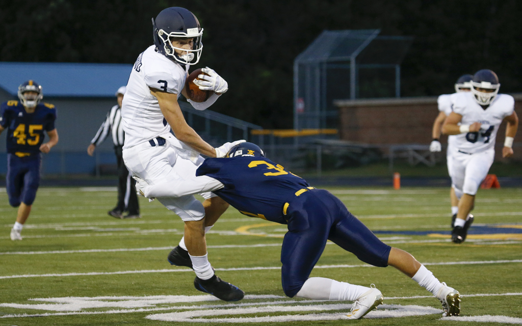 St. Thomas Academy's Gabe Sirek (3) tries to break the tackle of Mahtomedi's Nicolas Weisner (31) Friday night. Sirek had a TD reception in addition to kicking a field goal and five extra points for the Cadets. Photo by Jeff Lawler, SportsEngine