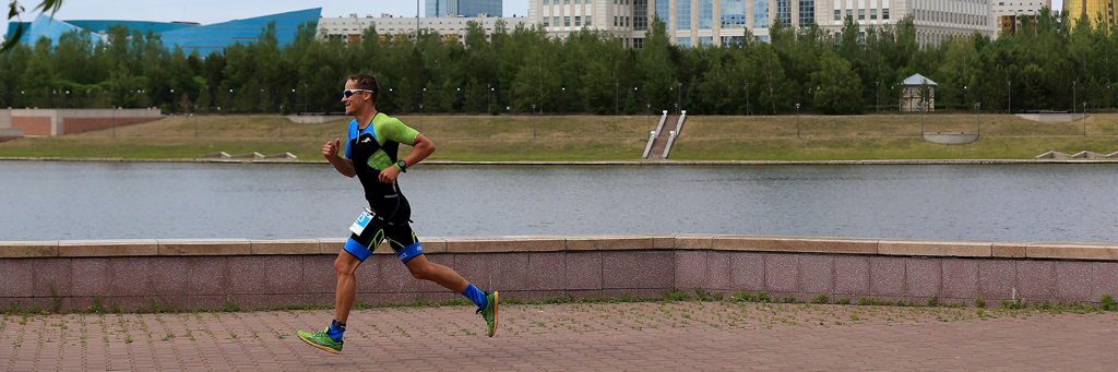 Athlete running through Astana Triathlon Park next to Ishim River