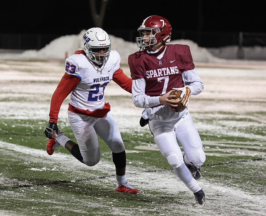 Quarterback Ryan Miles (7) looks for a receiver while evading an SMB defender. Miles threw five touchdown passes in a 42-28 win at Richfield High School on Thursday night. Photo by Cheryl A. Myers, SportsEngine