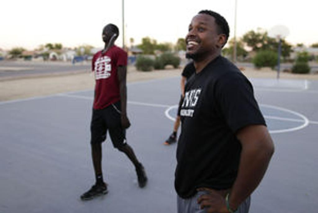 Team M'Phasis basketball coach Will Roberts watches as his players try to shoot three-pointers at the Jerry & Helen Wisotsky Boys and Girls Club Peoria Branch. The team focuses on character building and community as well as teaching local youth the fundam