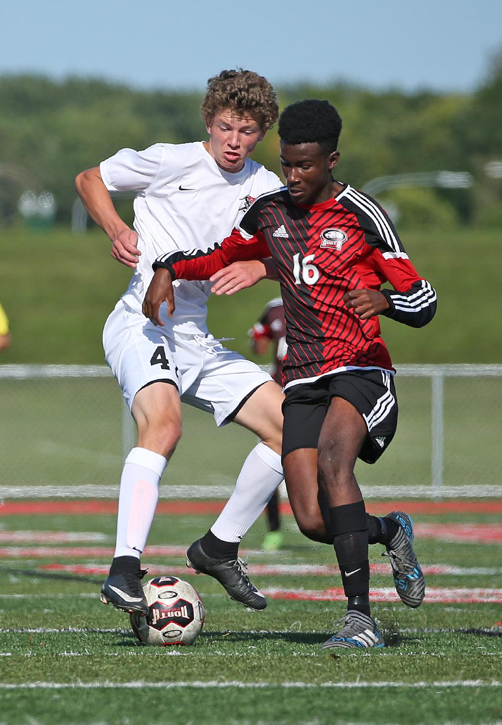 Ahmad Jalloh (16) battles for possession at midfield with Zach Lanigan. Jalloh scored the Polars' only goal in a 2-1 overtime loss to the Greyhounds at Polar Field in North St. Paul. Photo by Cheryl Myers, SportsEngine