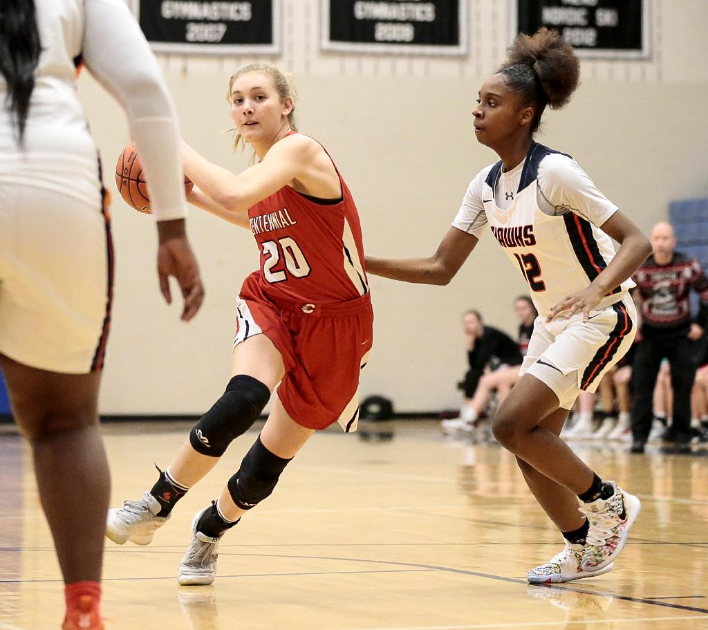 Centennial's Jodi Anderson (20) drives the lane past Robbinsdale Cooper defender India Kirkwood (12). Anderson tallied 16 points in the Cougars' 69-41 victory over the Hawks. Photo by Cheryl A. Myers, SportsEngine