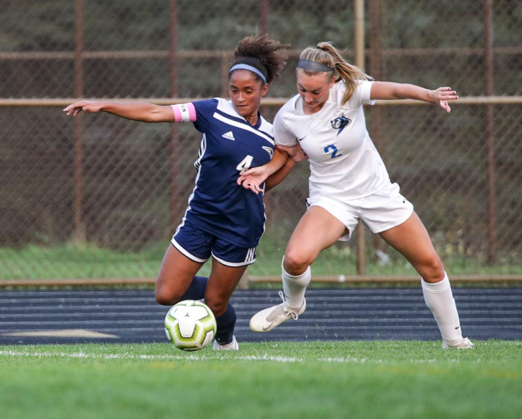 Senior captain Maille Mathis (4) and Mackenzie Matthies (2) race to the ball. Mathis, the Rebels' leading scorer this season, found the back of the net late in the game to give Champlin Park a 3-2 win. Photo by Cheryl A. Myers, SportsEngine