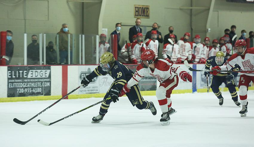 Hayden Klem dashes across the ice, trying to maintain possession of the puck with Luke Miller from Regis Jesuit challenging. Klem scored two goals in the Mustangs' 5-4 overtime defeat to the Raiders on April 1. Photo by Katie Hinkle, SportsEngine