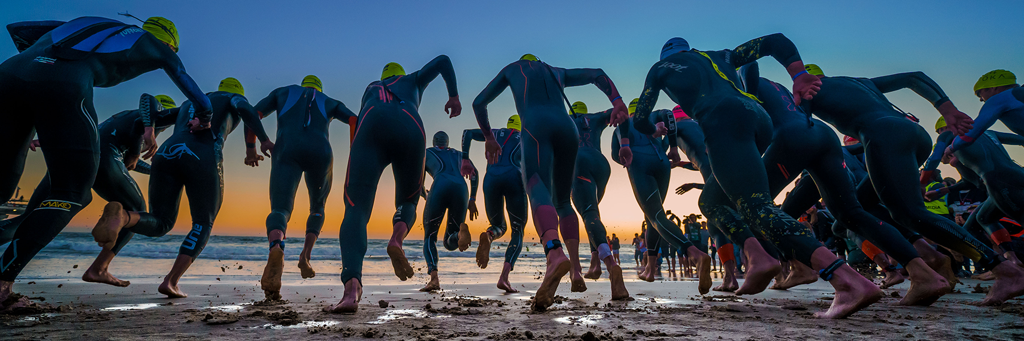 Close-up from below of IRONMAN African Championship athletes running into the sea at Hobie Beach at sunrise