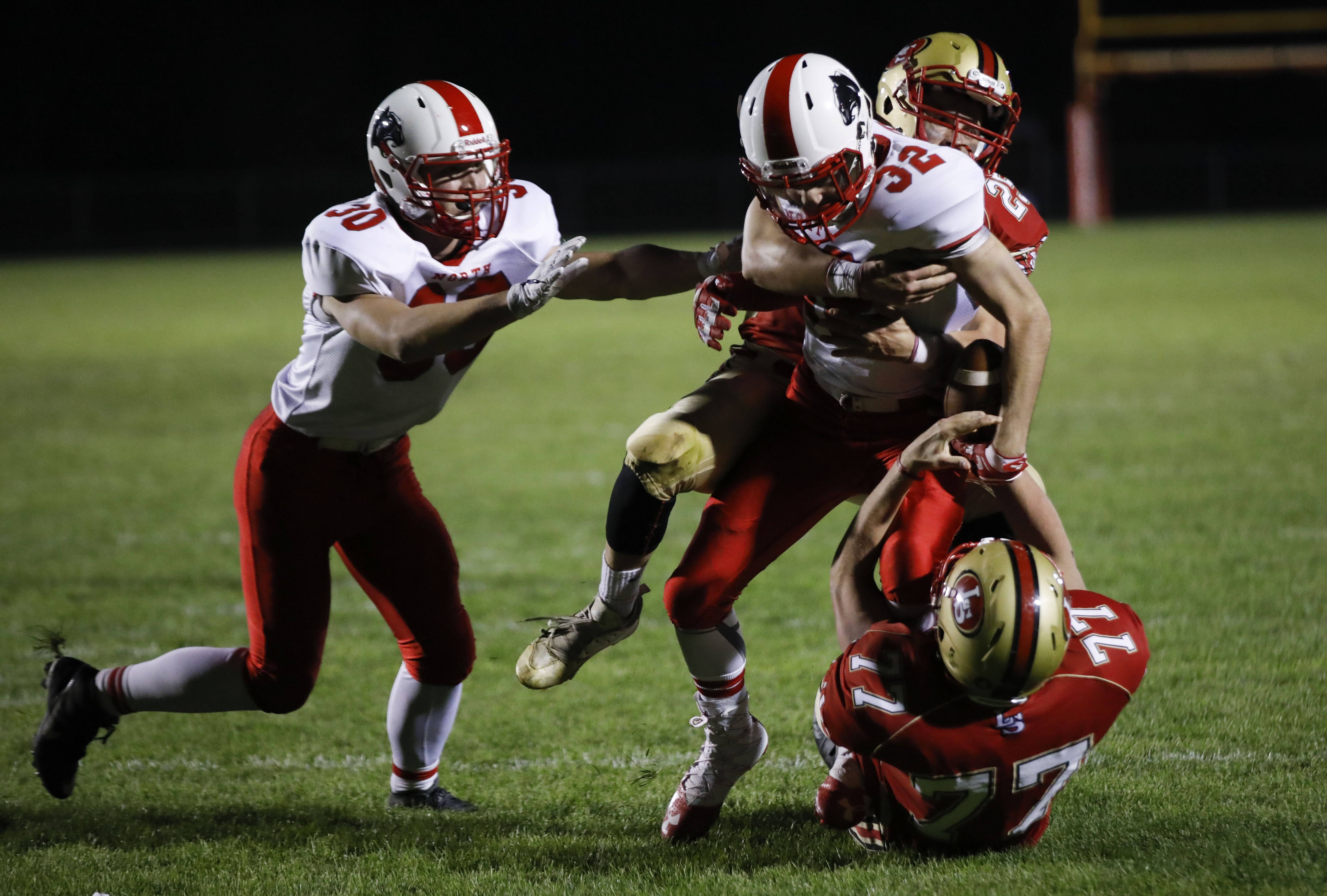 Jack Branson (32) of Lakeville North is tackled by Carter Hagen (25) and #77 of Lakeville South. Lakeville North defeated rival Lakeville South 35-0 away. Photo by Chris Juhn