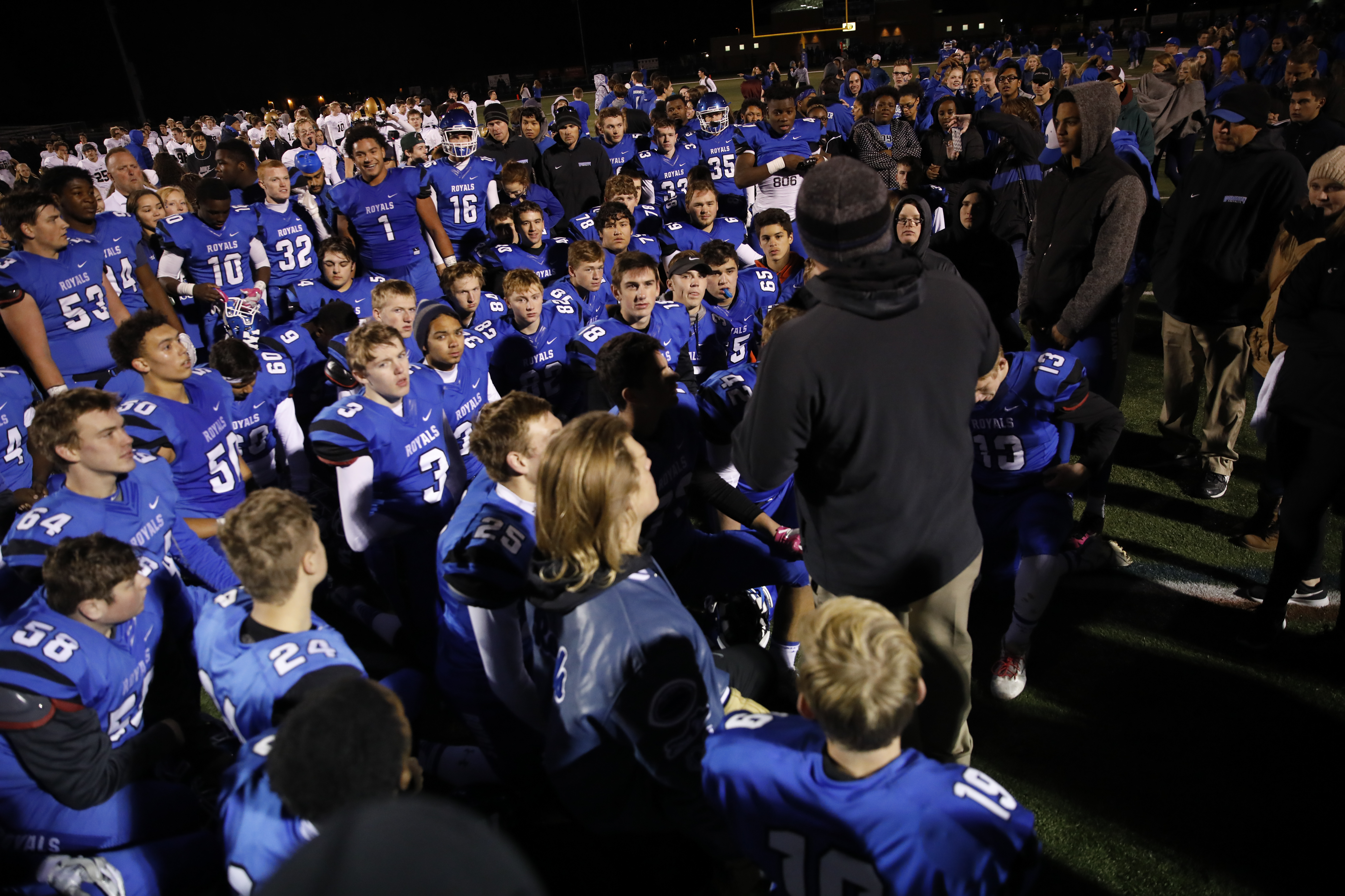 Woodbury players listen to the coach talk after they won the game 47-25 at home. Photo by Chris Juhn