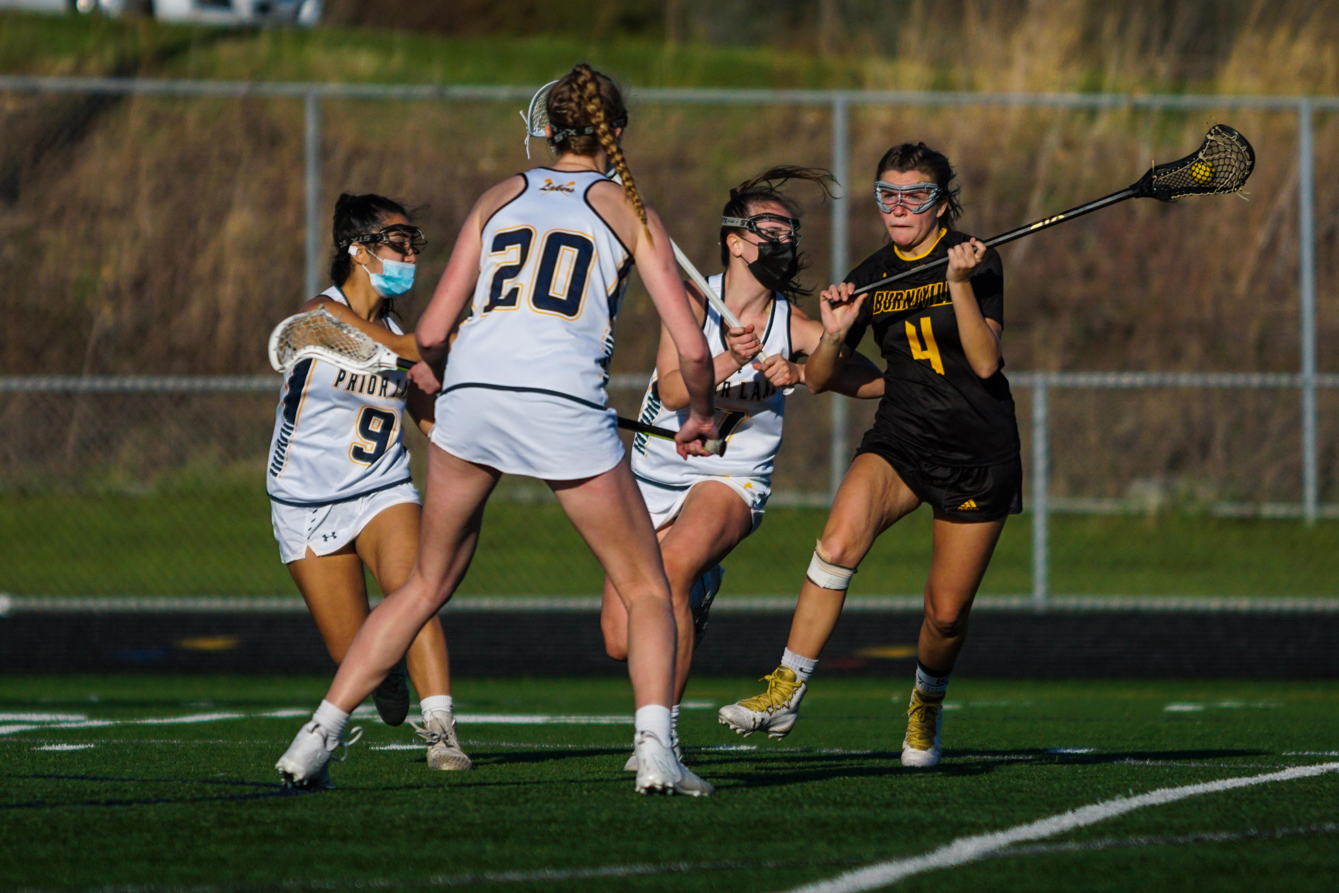 Apple Valley/Burnsville's Taiva Reinertson (4) is swarmed by Prior Lake defenders during a matchup Thursday. Reinertson had two of her team's goals in a 16-3 loss to Prior Lake. Photo by Korey McDermott, SportsEngine