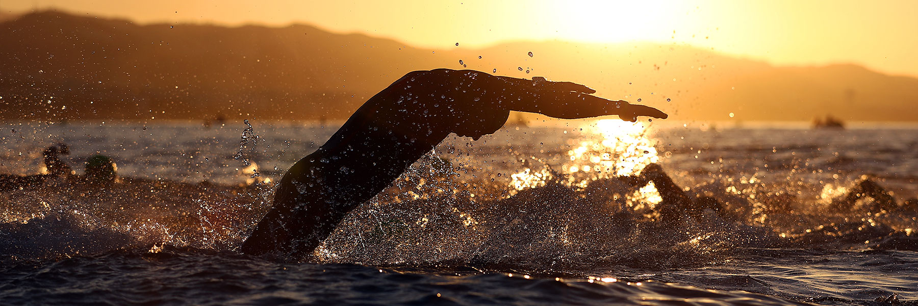 View of a single hand of an athlete swimming in the Mediterranean sea while the sun rises at IRONMAN 70.3 Marbella