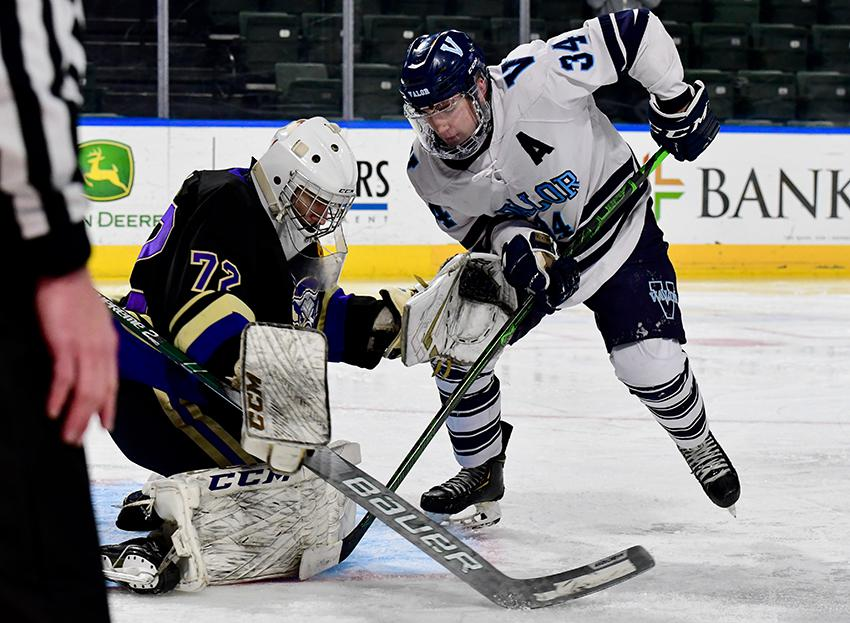 Sam Simon (left) fights for control of the puck with Valor Christian's Ryder Price (34) during Thursday's Class 5A state championship game in Loveland. The Lambkins lost 4-3 to the Eagles. Photo by Steven Robinson, SportsEngine