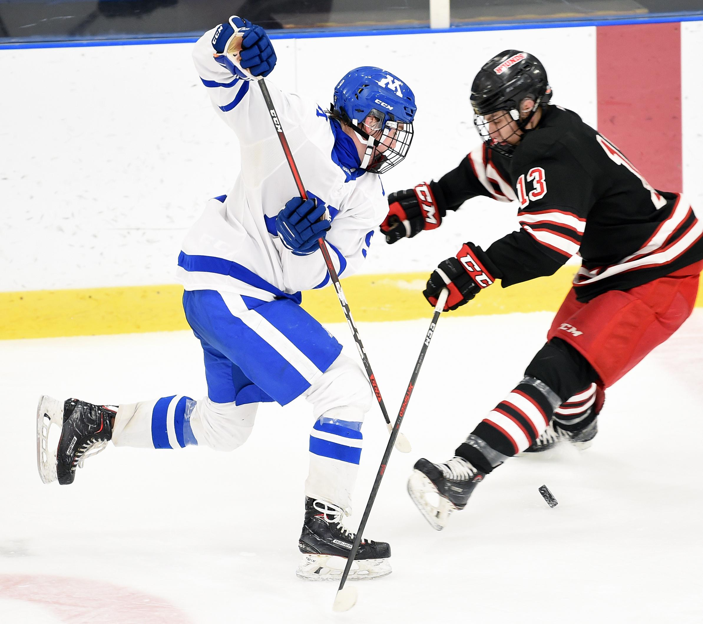 Minnetonka's Graham Harris, left, attempts to avoid the outstretched leg of Duluth East's Tyler Smith. Photo by Loren Nelson, SportsEngine
