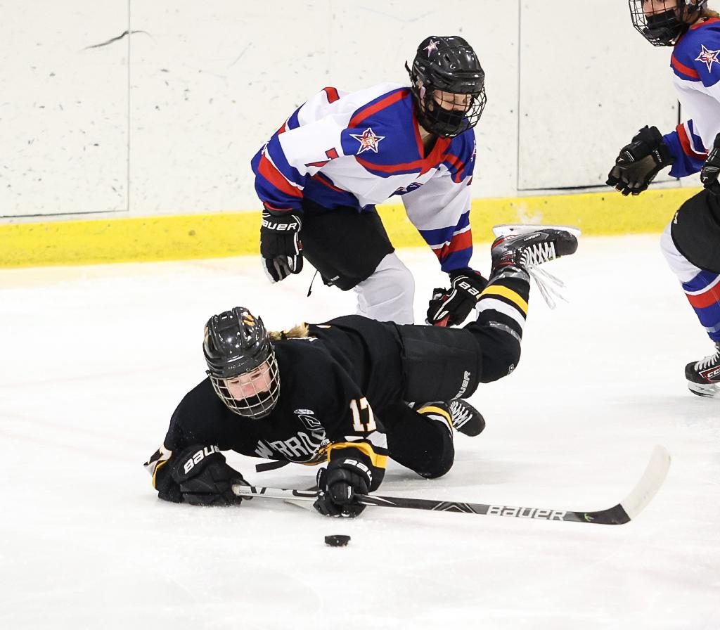 Warroad's Genevieve Hendrickson (17) is tripped by Cara Sajevic (7) early in the first period. Hendrickson, the Lady Warriors' leading scorer this season, scored their only goal of the game. Photo by Cheryl A. Myers, SportsEngine