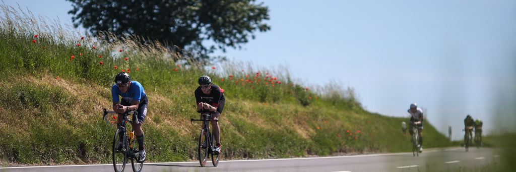 Athletes on their bike passing by a red poppy field at IRONMAN 70.3 Kraichgau