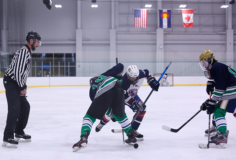 Mountain Ice's Pierson Klem (19) fights for control of the puck following a faceoff Friday evening. Klem scored a goal in his team's 6-2 loss to Cherokee Trail in Littleton. Photo by Katie Hinkle, SportsEngine
