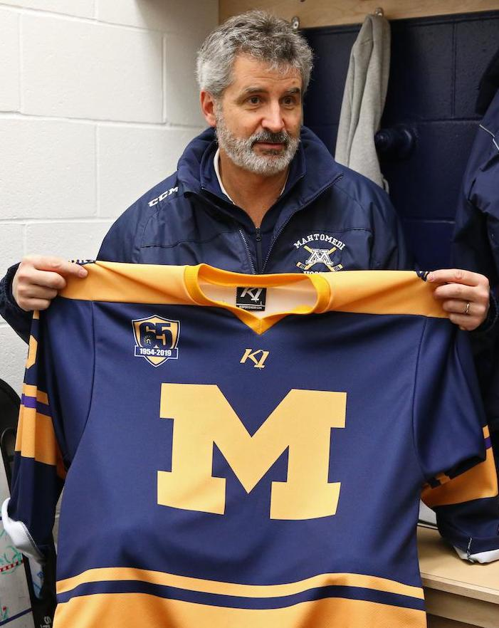 Mahtomedi coach Jeff Poeschl holds up the 2018-19 Zephyrs' home sweaters, which are designed to resemble the program's first uniforms in 1955-56.  Photo by Cheryl Myers, SportsEngine