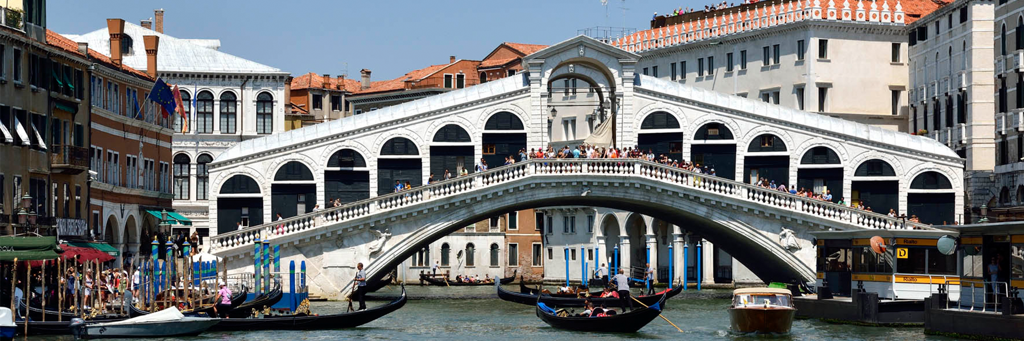 Famous white Rialto bridge in Venice, which is crossed by many tourists and under which a few gondolas pass