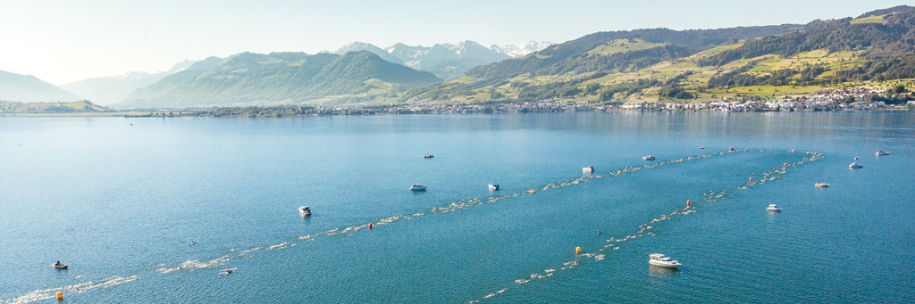 IRONMAN 70.3 Switzerland athletes taking on the swim course in the pristine waters of Obersee surrounded by hills of woods